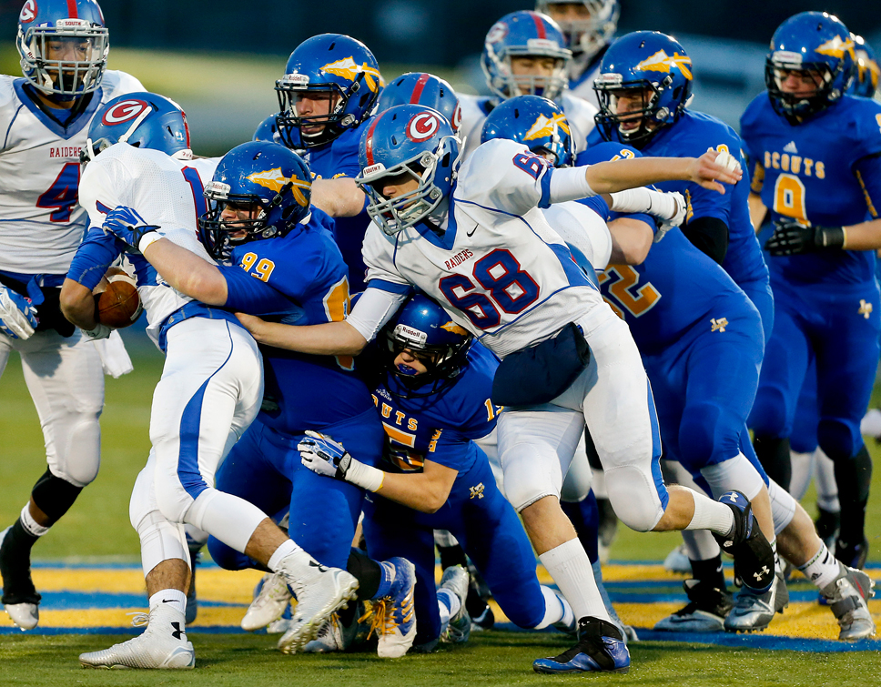 The gang's all here: Lake Forest High School nose guard Nicholas Athenson (No. 99) tackles Glenbard South's Jimmy Ebbole during second round state playoff action. Photography by Joel Lerner