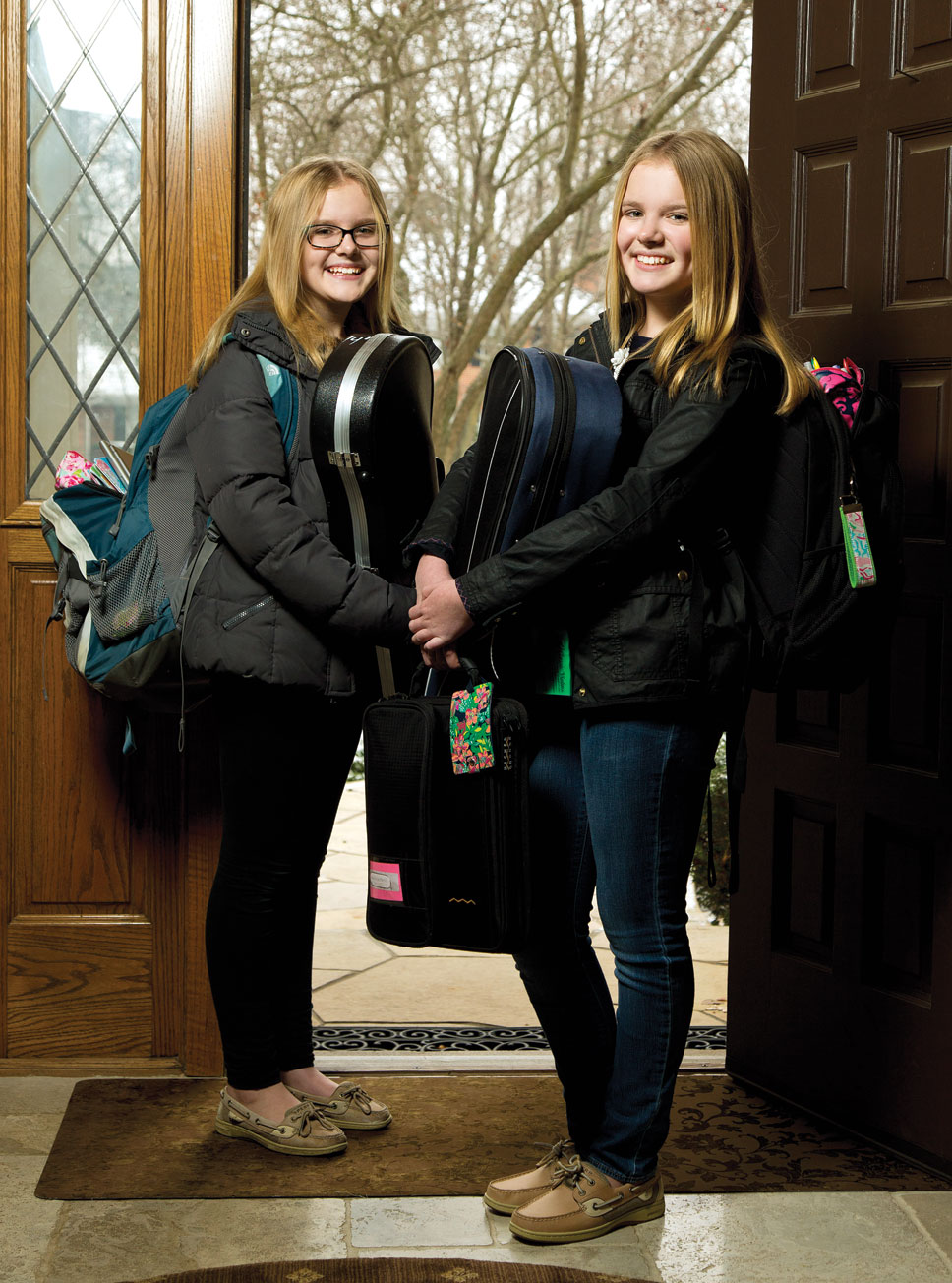Alexandra and Hayley Zarek, two of the Zarek triplets, carry their backpacks and violins to Deer Path Middle School every day. Photography by Joel Lerner