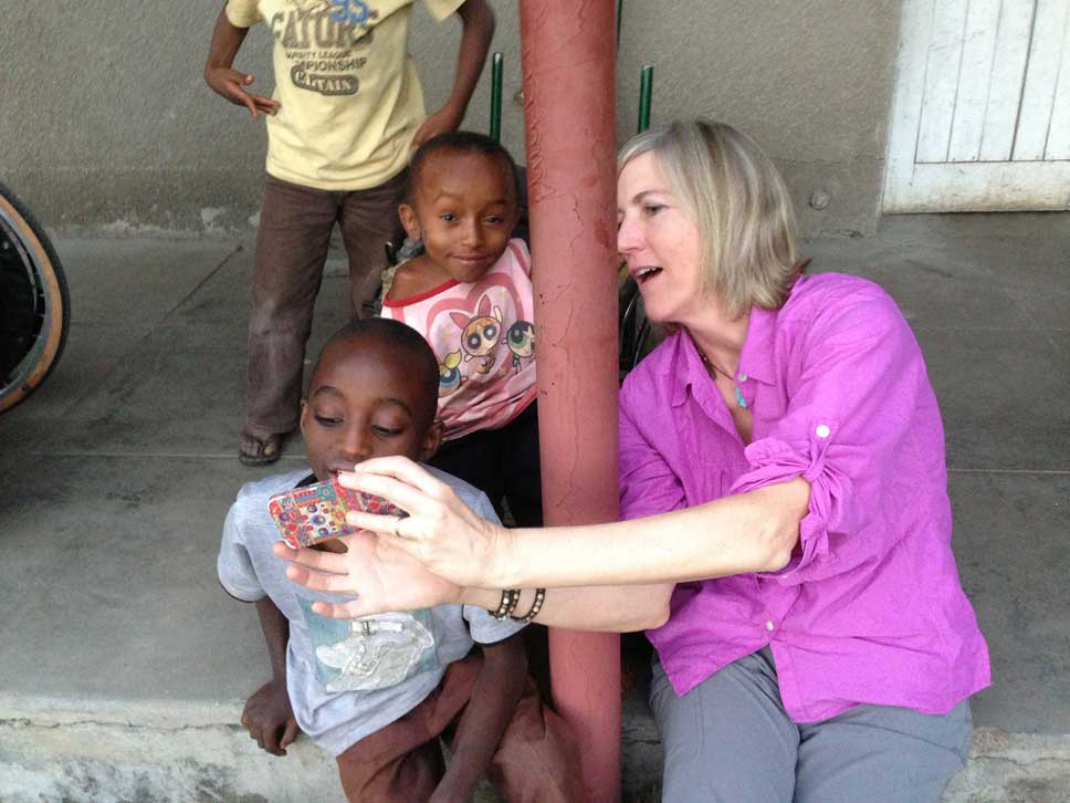 Meg Barnhart shows pictures to her new Faraja friends.