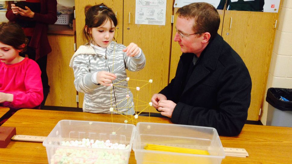 Adriana works with her father on a marshmallow tower.