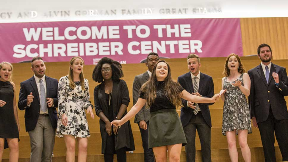 Loyola student a cappella group performs on the Gorman Great Stairs as guests leave Schreiber Center.