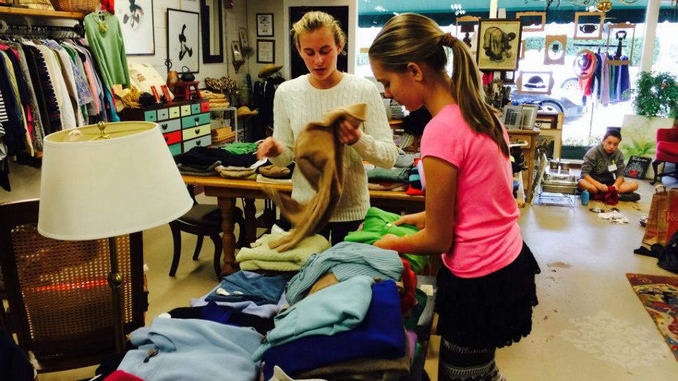 Folding sweaters at Forest & Found as part of Deer Path Middle School Community Service Day are (from left) Kate Gotta and Alex Slomba.