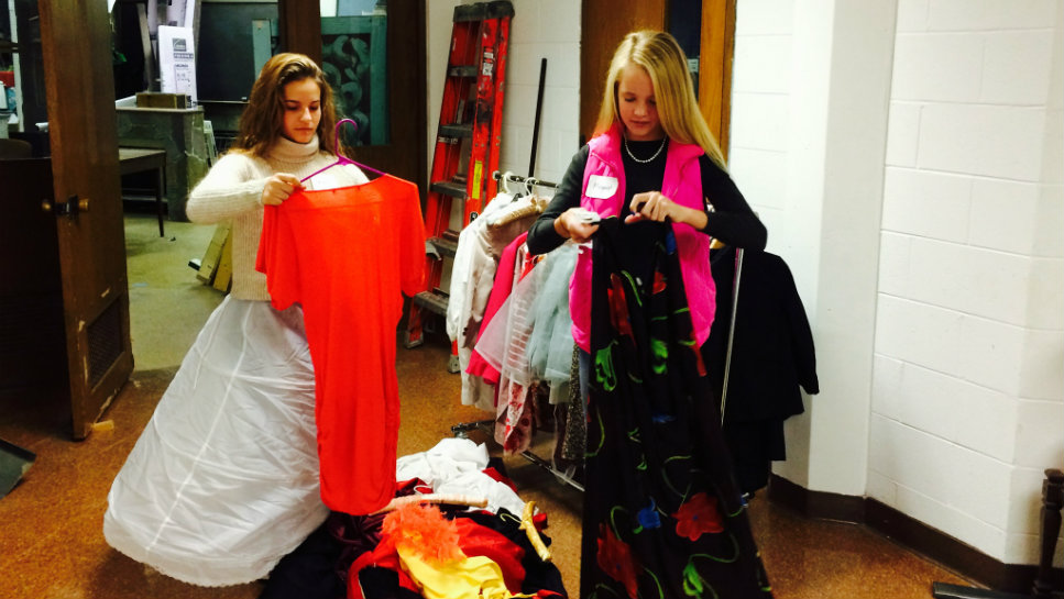 Deer Path Middle School students Mary Xakellis (left) and Margaret Matson organize costumes at the Citadel Theater as part of the school's Community Service Day.