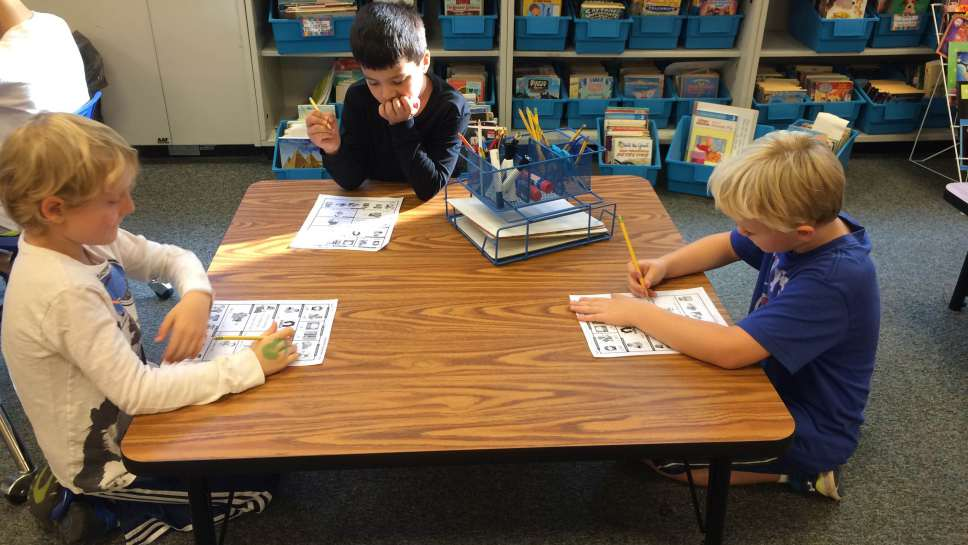 McKenzie Elementary School students kneeling at a new table.