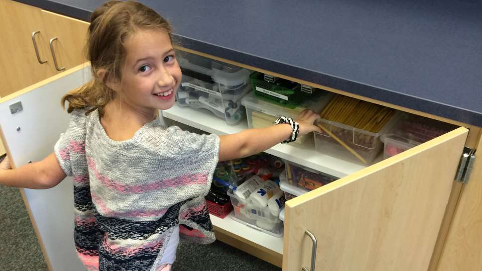 A student accessing supplies in a low cabinet.