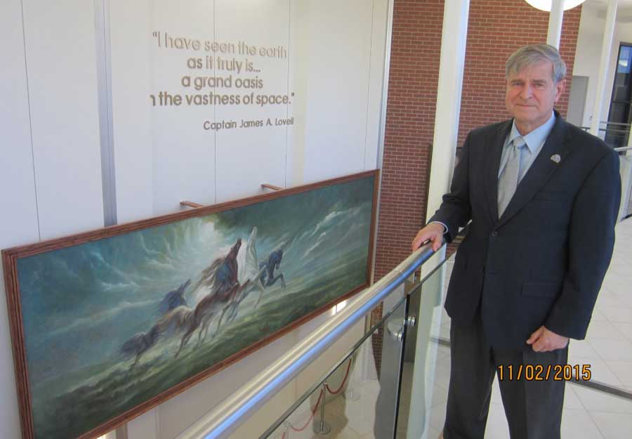 """Dr. Stephen R. Holt, director of the Capt. James. A. Lovell Federal Health Care Center, with """"Steeds of Apollo"""" artwork that used to hang over the bar at the former Lovell's restaurant in Lake Forest. The painting was a gift to the center by the Lovells."""