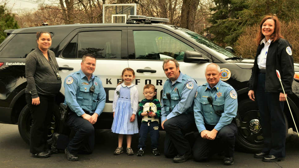 Liam and Sarah with the LFPD; from left; Police Officers Misa Maj; Brett N. Marquette; Big sister Sarah; Liam; Officer Steve Huck: Commander Rick Anderson; and Police Administrative Assistant Barb Lueder=Manetti; photo by Josephin Loch