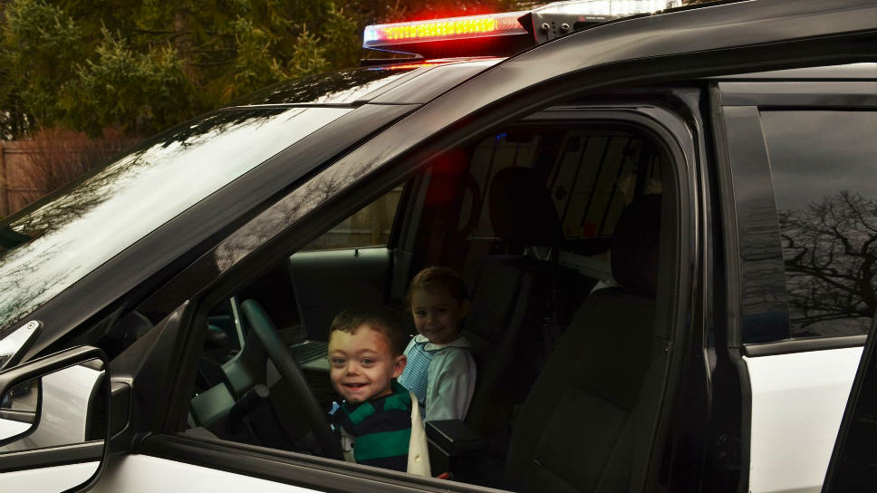 Liam and Sarah testing out the squad car; photo by Josefin Loch.