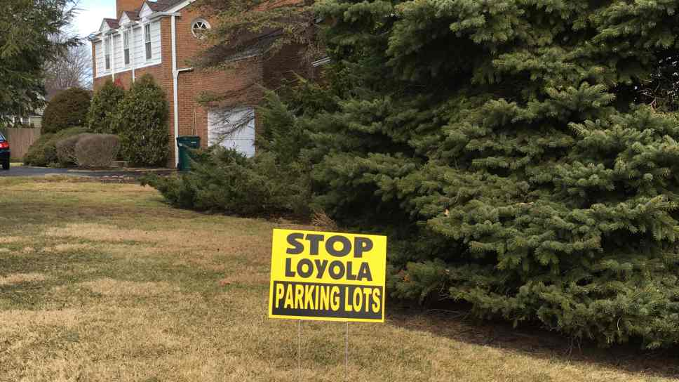 A yard sign protesting proposed parking lots at Loyola Academy.