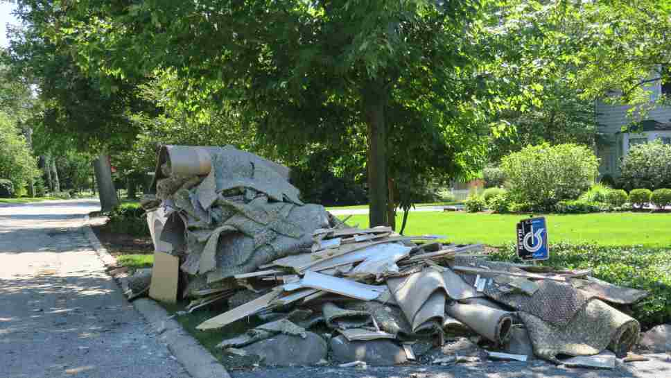 Carpeting and other damaged debris placed at the curb after a rainstorm caused flooding in Winnetka.