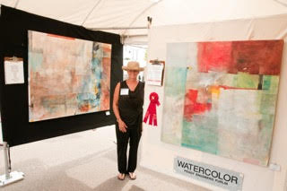 Standing between paintings in her booth is Peggy Furlin. Photo Courtesy of Rob Kuehnle.