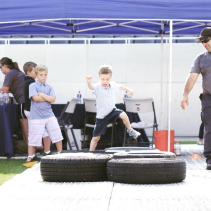 Youngsters high step through tires on an obstacle course run. Photo courtesy of Thrive Project for America.