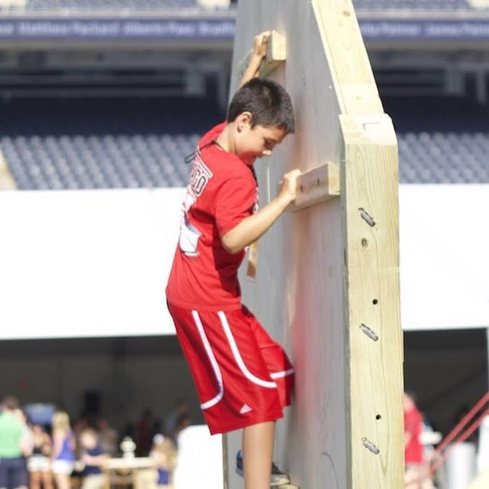 A young boy climbs an obstacle course wall. Photo courtesy of Thrive Project for America.