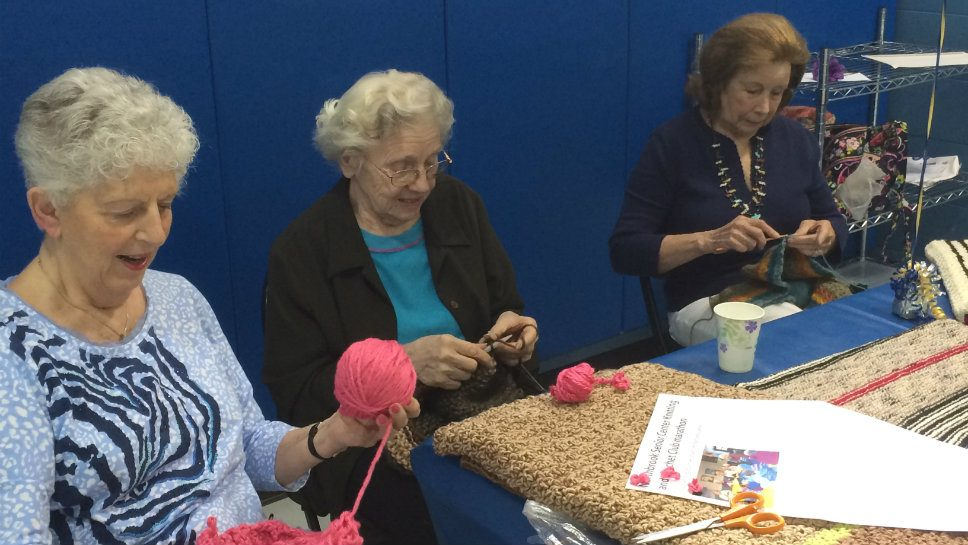 Telling visitors to the Northbrook Senior Center activities fair about the knitting and crocheting group are (from left) Phyllis Kosner, Clara Mueller and Lee O'Mara.