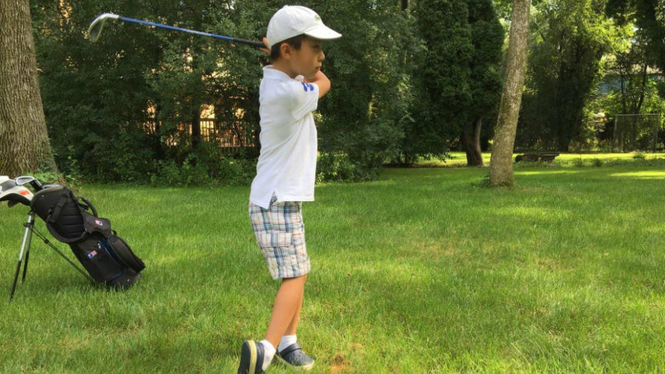 Connor Tzau works on his golf game in the backyard. Photo courtesy of David Tzau.