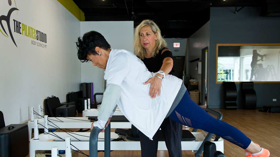 Head Instructor Rosey Kessler with co-owner Chai Duncan on a Pilates reformer