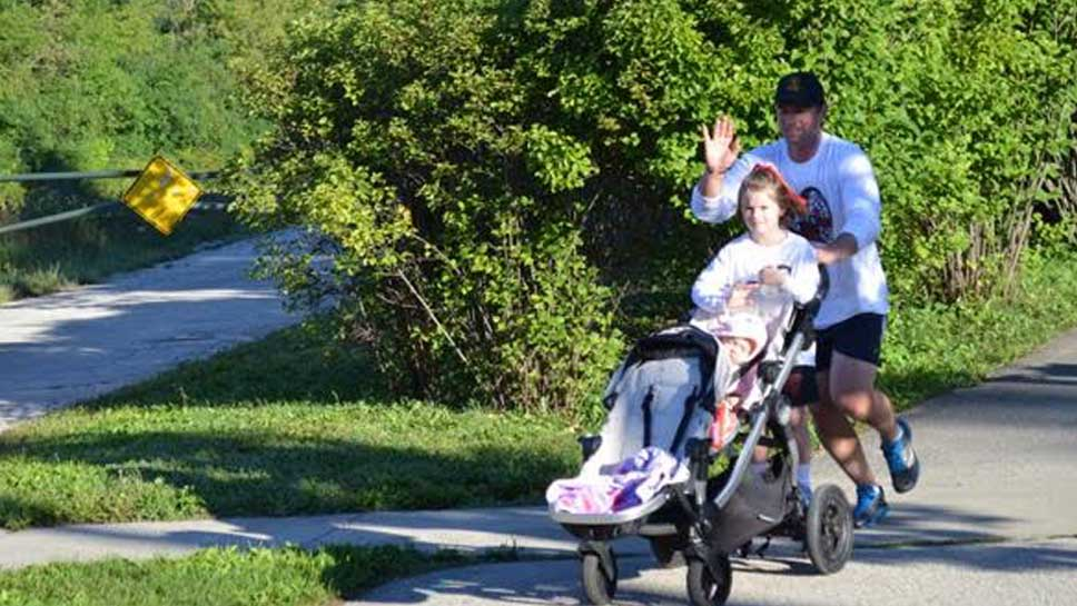 Matt Schachman of Winnetka pushes two of his four children in the 5K