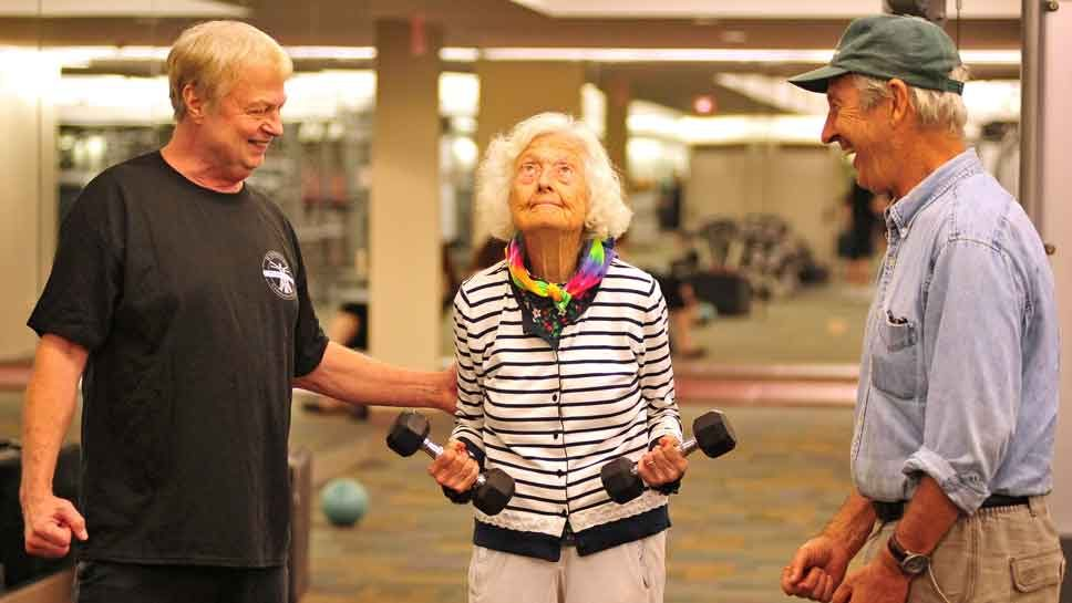 Nancy does dumbbell curls with support from her personal trainer Bob Davis (left) and her son Stuart Jones (right), during a session at the Winnetka Community House fitness center. PHOTOGRAPHY BY STEVE HANDWERKER/JWC MEDIA