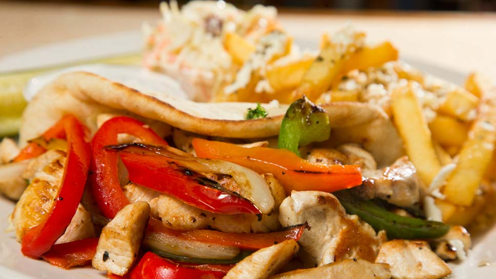 Greek Chicken Pita, Greek seasoned strips of chicken breast with peppers and onions served on a warm pita topped with tzatziki sauce (gyros sauce) and Greek fries at The Landmark Inn Bar and Grill in Northbrook. PHOTOGRAPHY BY JOEL LERNER/JWC MEDIA