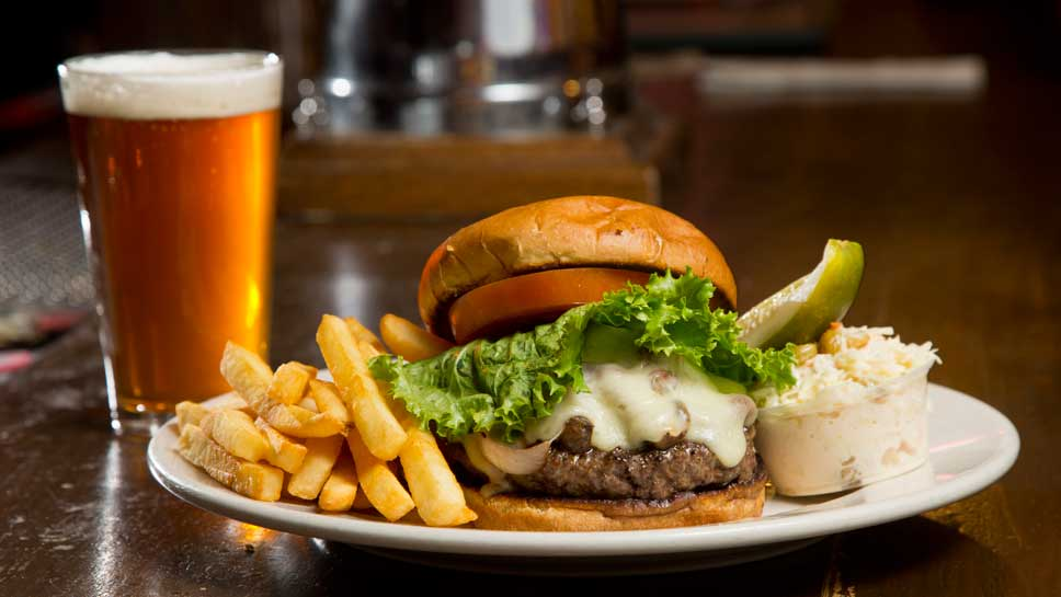 """The Montreal Steak Burger 1⁄2 pound burger rubbed with """"Montreal Steak Seasoning"""" topped with grilled Onions & mushrooms in a red wine reduction & provolone cheese"""