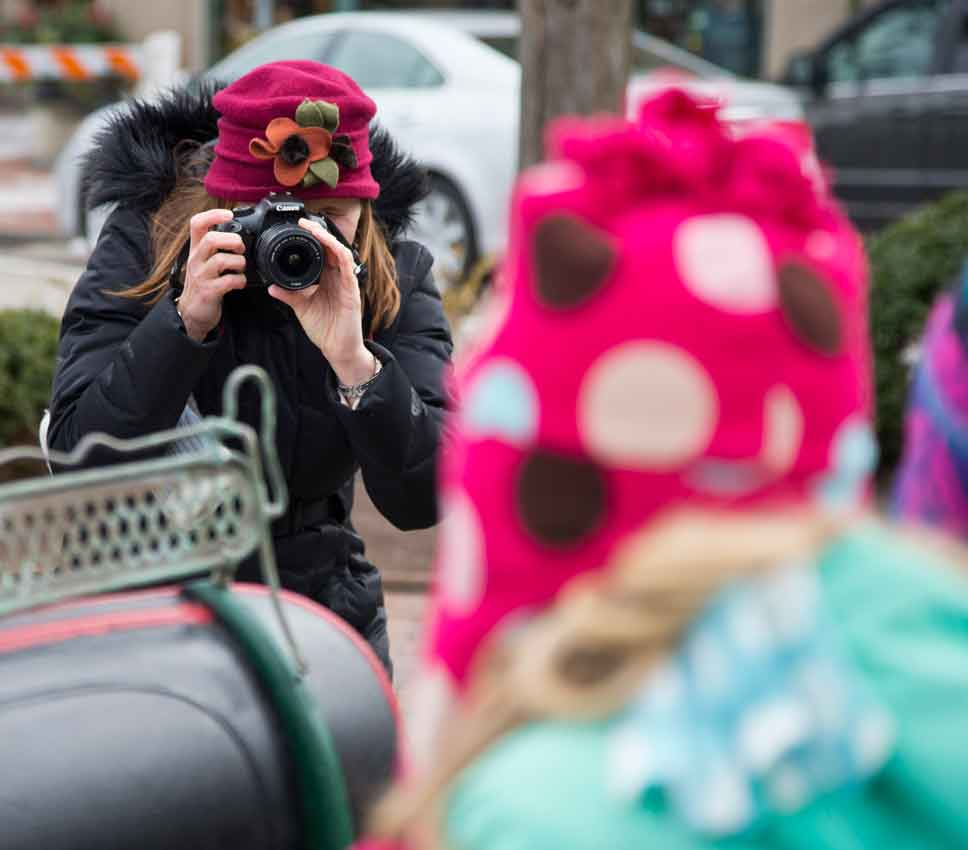 Emily McBean of Lake Bluff takes a photo of her kids in a sleigh at Market Square in Lake Forest on Saturday, December 10. Photography by Joel Lerner/JWC Media
