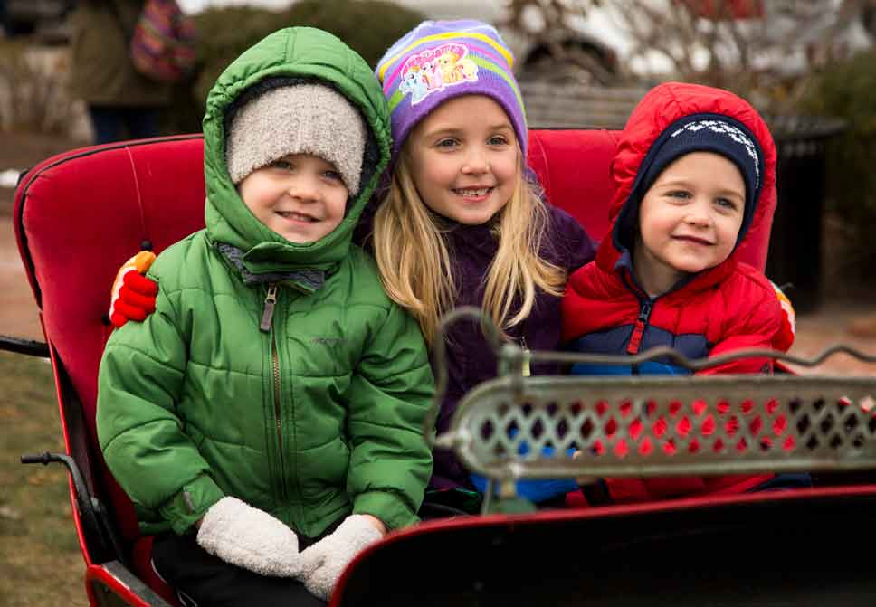 Delan, 4, Noa, 6, and Dillon, 4, Burke of Lake Forest pose in a sleigh at Market Square in Lake Forest on Saturday, December 10 . Photography by Joel Lerner/JWC Media