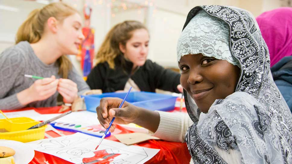 10 year old Sana Musa of the Sudan with Glenbrook South's Key Club members Freshman Gwen Skyles and Sophomore Yvonne Fondrevay during their visit to Refugee 1 in Andersonville. Photography by Joel Lerner/JWC Media