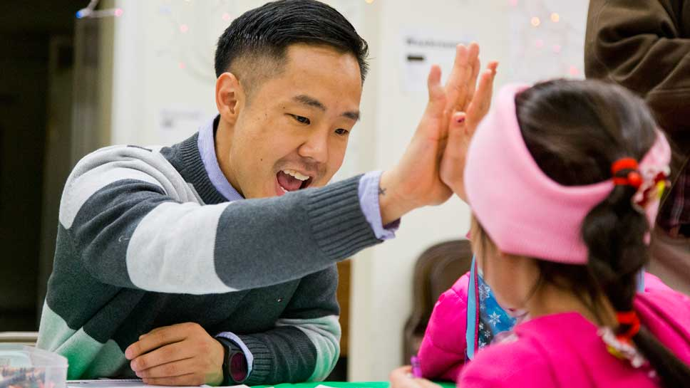 Glenbrook South's Key Club sponsor Josh Koo, a science teacher, gets high five during homework help during the GBS visit to Refugee 1 in Andersonville. PHOTOGRAPHY BY JOEL LERNER/JWC MEDIA